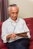 Starsza męska używa technologia dla rozrywki Obrazy Royalty Free