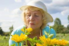 Starsza ogrodniczka relaksuje ogrodowych kwiaty i wącha zdjęcia royalty free