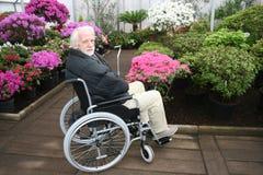 Starsza ogrodniczka w koła krześle i jego pracujemy Zdjęcia Royalty Free