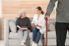 Starsza osoba mężczyzny mienia chodząca trzcina i zamazany opiekun z starszą kobietą na tle, ostrość na ręce obraz royalty free