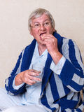 Starsza osoba mężczyzna kładzenia dentures wewnątrz Obraz Stock
