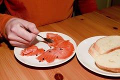 Starsza osoba mężczyzna mienia łasowanie i rozwidlenie dymiliśmy łososia z plasterkiem biały chleb Samotność i pojedynczy pojęcie Fotografia Stock