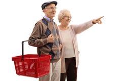 Starsza osoba mężczyzna mienia zakupy kosz z starszy kobiety wskazywać Fotografia Royalty Free