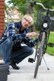 Starsza osoba mężczyzna naprawiania bicykl fotografia royalty free