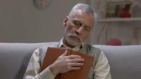 Starsza osoba mężczyzny dosypianie na kanapie podczas czytania, zanudza książkę, brak interes zbiory