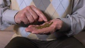 Starsza osoba mężczyzny liczenia monety w otwartej palmie, ubóstwo, niska emerytury korzyść zbiory