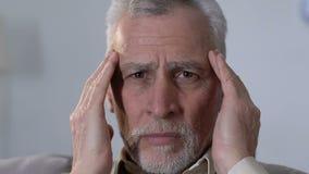 Starsza osoba mężczyzny masowania świątynie, cierpienie od migrena nieładu, problemy zdrowotni zbiory