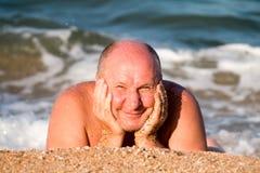 starsza osoba mężczyzny zezy od słońca lying on the beach na piasku w morze pianie i wygrzewać się w falach fotografia stock
