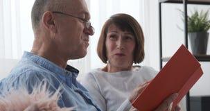 Starsza para śmia się podczas gdy czytelnicza książka w domu zbiory