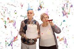 Starsza para świętuje urodziny z rogami i przyjęcie kapeluszami Obraz Royalty Free