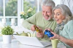 starsza para bawić się grę komputerową z laptopem podczas gdy pijący fotografia royalty free