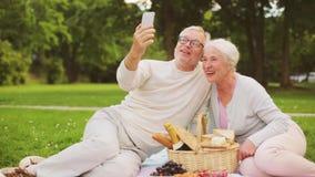 Starsza para bierze selfie przy pinkinem w parku zbiory