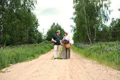 Starsza para chodzi przez lasu i mężczyzna daje kobiecie tkanemu koszowi z bukietem kwiaty purpurowi lupines Zdjęcia Stock