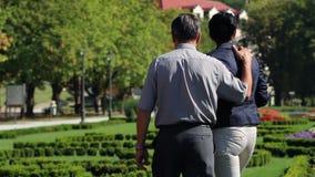 Starsza para cieszy się czas wolnego w parku i zbiera pięknych kwiaty zbiory wideo