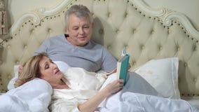 Starsza para czyta książkę w łóżku zdjęcie wideo