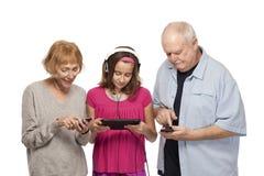 Starsza para i wnuczka z cyfrową pastylką p i wiszącą ozdobą Zdjęcie Stock