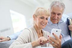 Starsza para ma zabawę używać smartphone Obraz Royalty Free