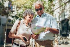 Starsza para patrzeje mapę podczas gdy zwiedzający Fotografia Royalty Free
