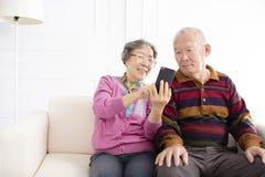 starsza para patrzeje telefon komórkowego obraz stock