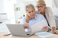 Starsza para robi administraci papierkowej robocie na laptopie wpólnie zdjęcie stock
