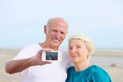 Starsza para robi jaźni fotografii na plaży Zdjęcie Stock