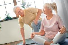 Starsza para robi joga opieki zdrowotnej motyliej pozie patrzeje na each inny wpólnie w domu Zdjęcia Royalty Free