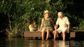 Starsza para siedzi blisko wody zbiory