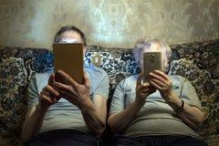 Starsza para siedzi na leżance z gadżetami, spojrzenie przy one zakończenie ich twarze zdjęcie stock