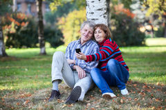 Starsza para siedzi wpólnie i robi selfie z telefonem komórkowym w parku Zdjęcia Stock