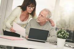 Starsza para sprawdza pieniężnego dokument Zdjęcie Royalty Free