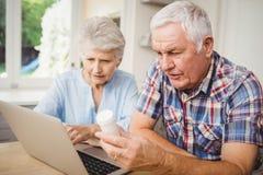 Starsza para trzyma pigułki butelkę podczas gdy działający laptop Zdjęcie Stock