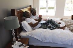 Starsza para używa laptop w sypialni podczas gdy pijący filiżanka kawy obrazy royalty free