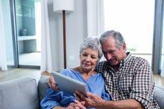 Starsza para używa cyfrową pastylkę na kanapie obraz stock