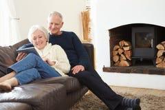 Starsza para Używa Cyfrowej pastylkę Na kanapie zdjęcia stock