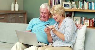 Starsza para używa laptop i trzymający kredytową kartę zbiory