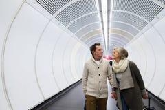 Starsza para w korytarzu metra ciągnięcia tramwaju bagaż Zdjęcia Stock