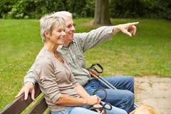 Starsza para wskazuje z palcem na parkowej ławce Fotografia Royalty Free