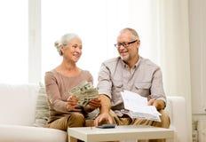 Starsza para z pieniądze i kalkulatorem w domu Zdjęcie Stock