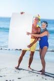 Starsza para z plażowym wyposażenia mieniem biały plakat Zdjęcia Stock
