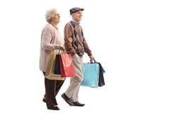 Starsza para z torba na zakupy chodzić Zdjęcia Royalty Free