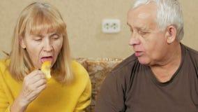 Starsza pary łasowania owoc na leżance w domu Kobieta ciie daleko kawałek persimmon i daje mężczyzna nadwaga Zdrowy zbiory wideo