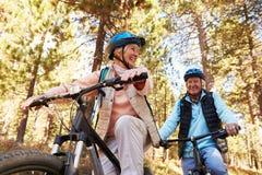 Starsza pary góra jechać na rowerze na lasowym śladzie, niski kąt Fotografia Stock