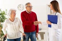 Starsza pary wizyty lekarka o student medycyny konsultaci zdjęcia stock