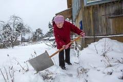 Starsza samotna kobieta czyści śnieg blisko jego wiejskiego domu Zdjęcia Stock