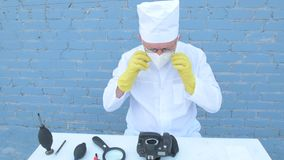Starsza stała osoba w białej opatrunkowej todze, nakrętka, medyczna maska, szkła czyści matrycę cyfrowa kamera z specjalnym znacz zbiory wideo