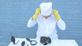 Starsza stała osoba w białej opatrunkowej todze, nakrętka, medyczna maska, szkła czyści matrycę cyfrowa kamera z specjalnym znacz zbiory