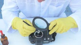 Starsza stała osoba w białej opatrunkowej todze, nakrętka, medyczna maska, szkła czyści matrycę cyfrowa kamera z specjalnym znacz zdjęcie wideo