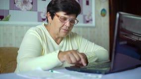 Starsza stara kobieta sprawdza koszty dzienni koszty na laptopie w domu w eyeglasses zbiory