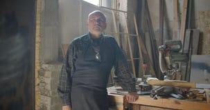 Starsza szara z włosami męska fachowa ciesielka mistrza pozycja przy drewnianą manufakturą z krzyżować rękami jest spokojny zbiory wideo