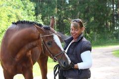 Starsza szczęśliwa kobieta i brown koń w lesie Obraz Royalty Free